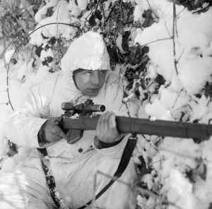 A_6th_Airborne_Division_sniper_on_patrol_in_the_Ardennes,_wearing_a_snow_camouflage_suit,_14_January_1945._B13676